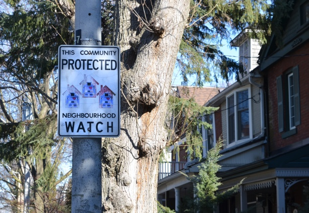 neighbourhood watch sign with 3 lovebot stickers on it