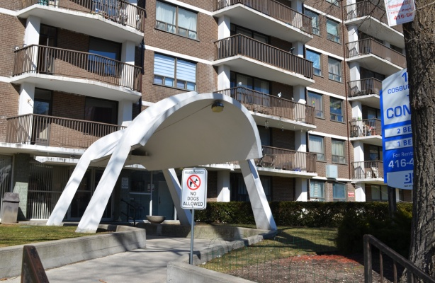 curved white concrete cover over entrance of apartment building, that is brown brick with white balconies