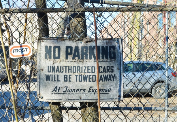 very old no parking sign on a chain link fence
