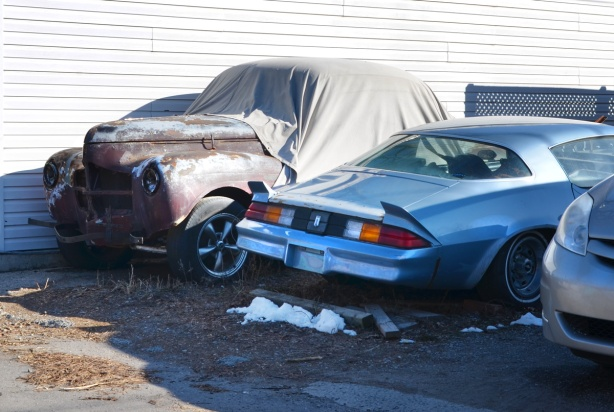 2 old cars in an alley. one is an old brown car from the 40's, under a cloth. the other is a blue camaro
