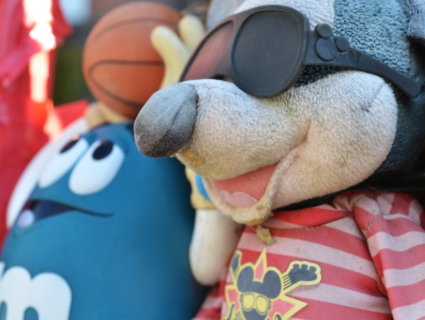 an old stuffed mouse with black plastic glasses, in front of a blue m & m character throwing a basketball, outside, and slightly weathered