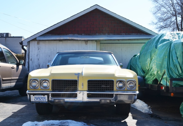 an old yellow Oldsmobile car, with historic licence plate, parked in a driveway in front of an old white garage