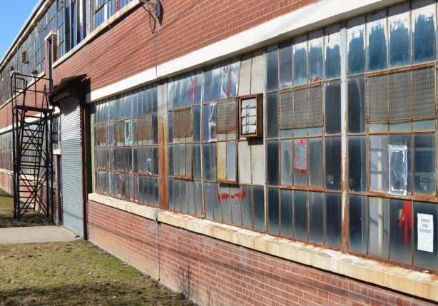 looking along the exterior wall of two storey brick building with long horizontal ribbons of window panes, many glass pieces are broken or cracked and then fixed with tape