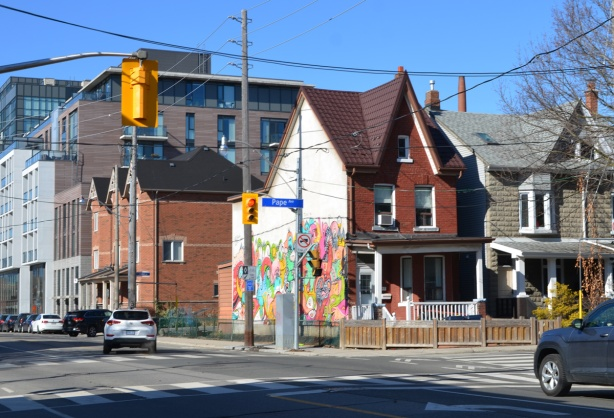 an intersection, looking northwest at Dundas and Pape where the house on the corner has a large mural by j. Chiale on the side, newer houses and apartment building in the background.