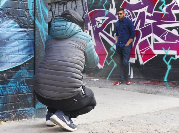 a man in a grey puffy jacket taking a picture of another man who is posing beside street art