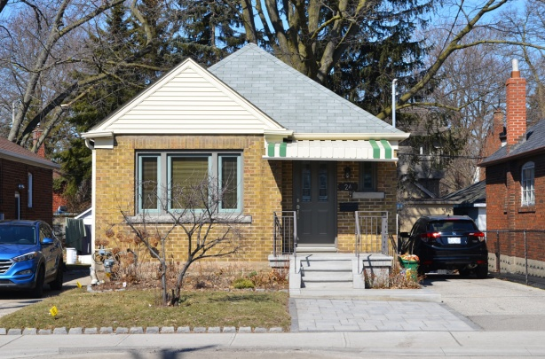 a well kept yellow brick post war bungalow with a grey roof and a partial white and green metal awning over the front steps that lead to a small porch