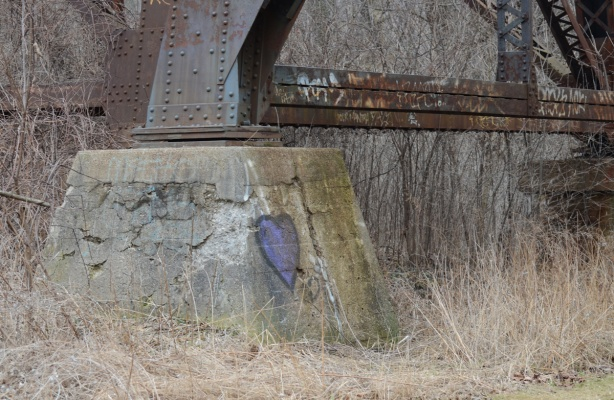 a purple graffiti heart painted on the concrete support at the bottom of a large metal trestle