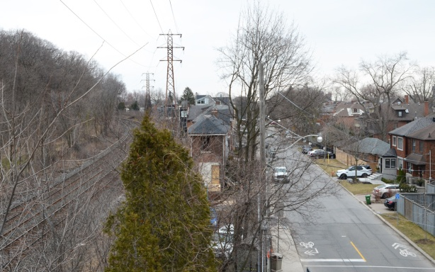 view from pedestrian railway bridge, Summerhill Ave., with houses, tracks, street, and trees, early spring