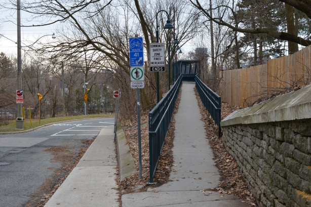 sidewalk splits, half goes to ramp up to a pedestrian bridge over the railway tracks and half follows the road that curves and goes under the bridge beside the tracks, blue railing