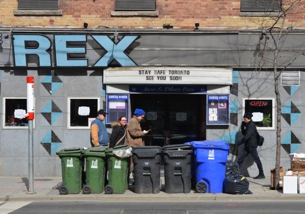 people walking past the Rex on Queen Street, has sign over door that says