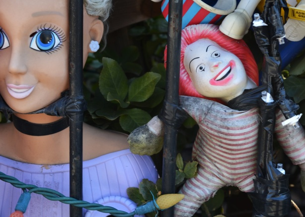close up of two of the dolls attached to the railing in front of house