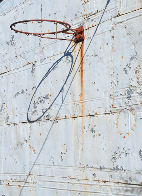 metal wall, painted white, exterior, with some rust, also an old basketball hoop and its shadow