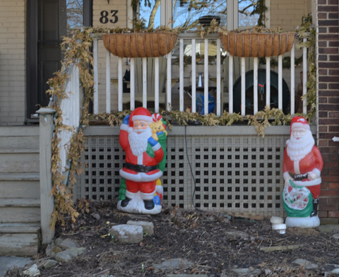 2 plastic Santa Claus figures in a front yard, no snow, in frontof a porch