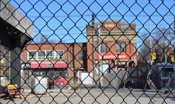 looking through a chainlink fence, across a vacant lot towards Queen Street east and the brick Scotiabank building