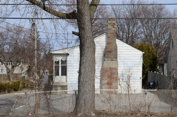old white bungalow with side fireplace and chimney wall, exterior