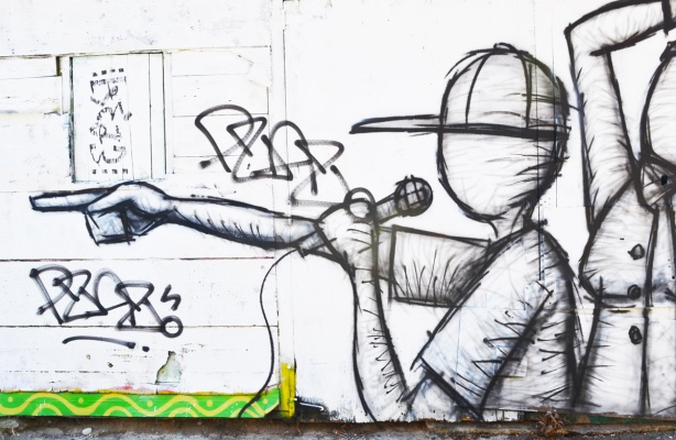 street art drawing in black of a person with baseball cap on, holding a microphone in one hand and pointing with the other hand
