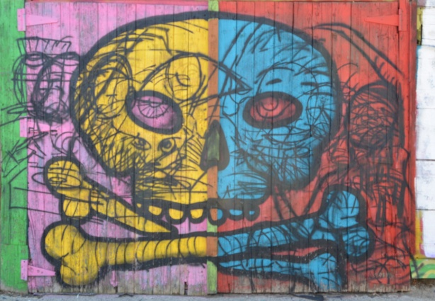 old wood garage door with street art of a skull and cross bones in bright colours, yellow, pink, blue, and orange