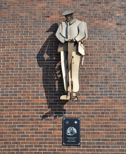 a metal statue of a soldier, at rest, mounted on a brick wall, as memorial to soldiers who committed suicide