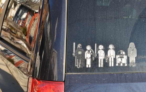a star wars sticker family on the back window of a black vehicle, 2 kids, an R2D2 and a wokie