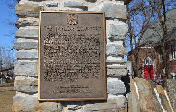 bronze plaque on a stone wall, Taylor cemetery, erected by the East York historical society gives rough outline of the history of the Taylor family here