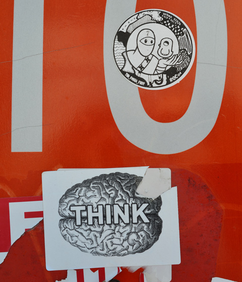 2 stickers on a stop sign. one is a picture of a brain with the word think on it. the other is an urban ninja squadron sticker