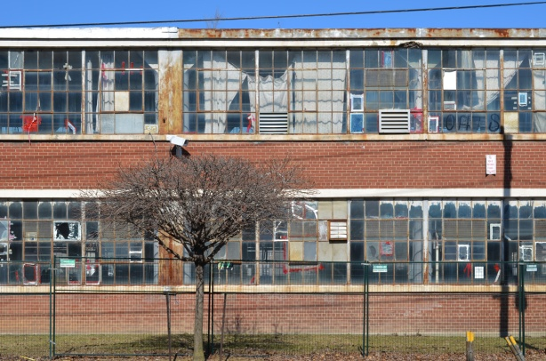 south wall of Parkhurst knitting mills, empty and abandoned, many glass panes cracked or broken, old curtains in the window