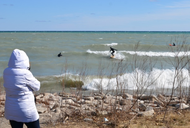 a woman in a white parka is watching men surf in rough waters and high waves of Lake Ontario