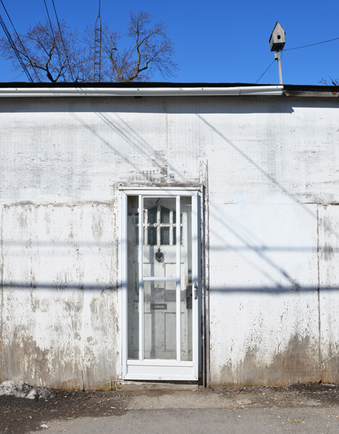 a white door on a white wall with blue sky, also a bird house above the roof, horizontal shadow across the front of the house