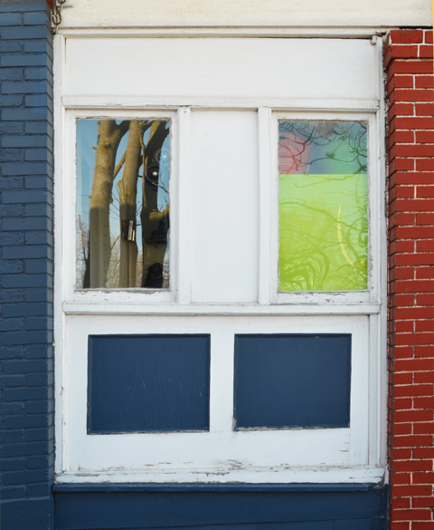 on the side of a house, a wood panel on porch with 2 windows, 2 panels are painted blue and the last one is white