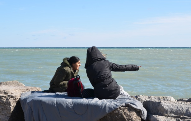 two women in winter clothes sitting on a blanket on rocks by the lake, one is pointing at something
