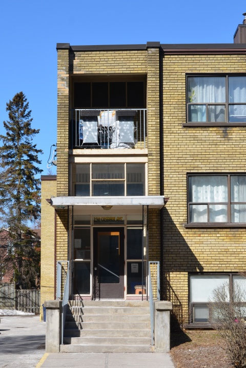 front entrance, exterior, of a yellow brick lowrise apartment building from the 1960s or 1970s