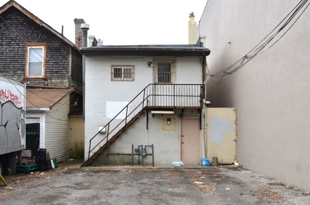 back of a small white building, store, in an alley, small porch on upper door with exterior stairs up to it