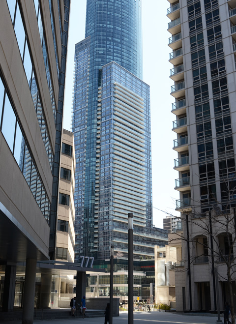 behind 777 college street at college and bay streets, large tall condo buildings with a park in between