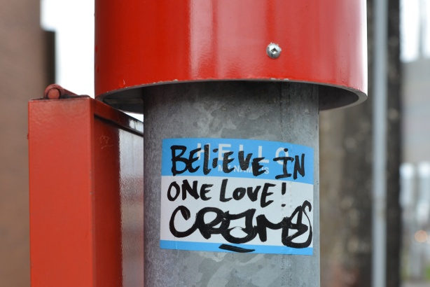 a sticker on a ttc bus stop pole that says believe in one love