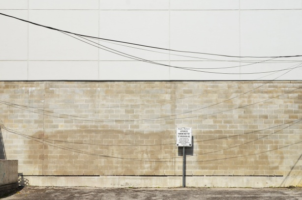 brick wall of a building beside a parking lot, with sign saying reserved parking