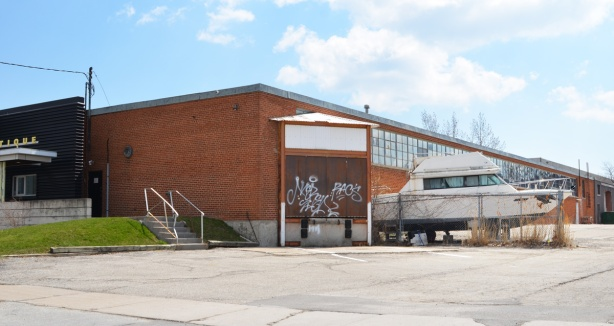 low rise brick light industrial building with an old boat parked beside it