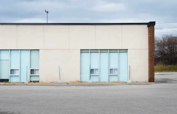 low one storey building with two large windows with blinds closed, no cars in parking lot