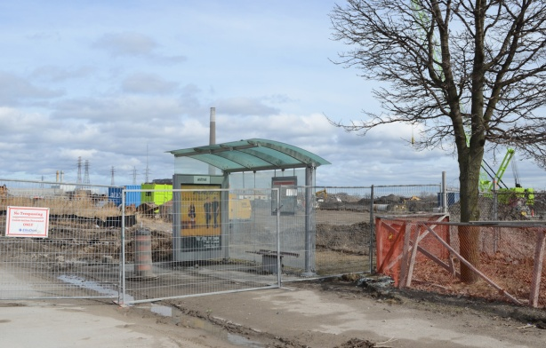 a glass bus shelter behind a construction fence