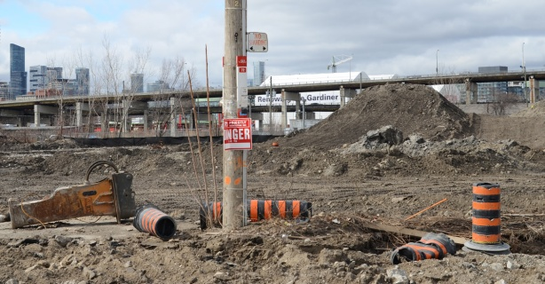 TTC bus stop for route 72 on Commissioners street but pole is now in the middle of a construction site, lots of dirt, orange and black traffic cones, Gardiner Expressway in the background