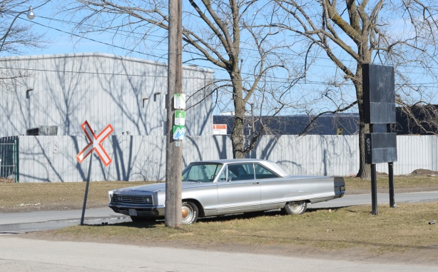 old car parked beside an old railway crossing sign, for a railway track that is no longer there