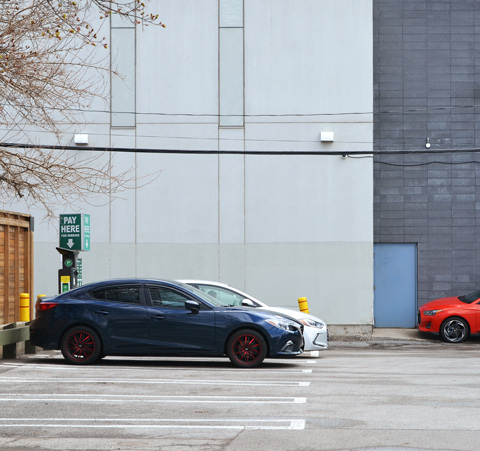 building beside a parking lot with three cars parked there, white car, blue car and red car