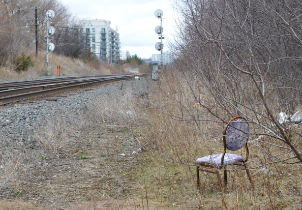 a lone chair sitting in the grass beside the railway tracks, shrubs behind the chair, early spring, no leaves on the shrubs