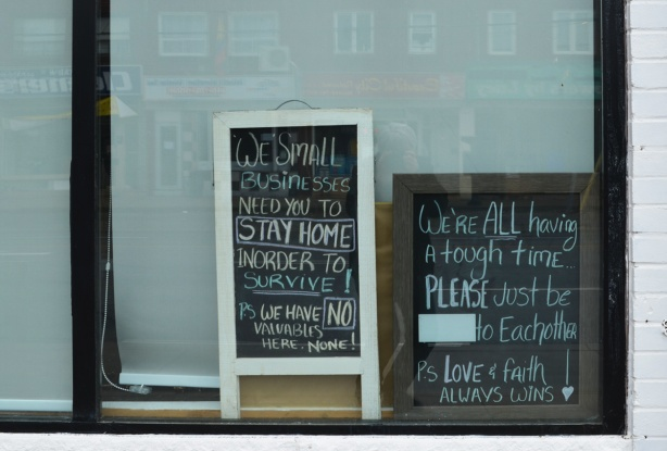 two chalkboard signs in the window of a store