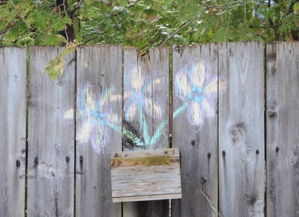 chalk drawing of three flowers growing out of a wood planter mounted on a wood fence