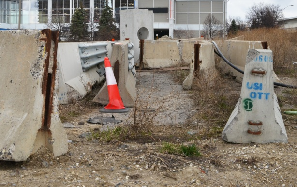 concrete barriers being stored on a vacant lot, one ornage and white cone too