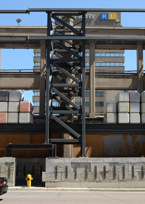 metal framework and concrete weights that are used to shore up the walls of a facade being saved during redevelopment
