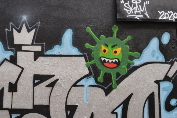 part of a mural in Graffiti Alley, a silver tag with a green corona virus with open mouth, white teeth and yellow eyes