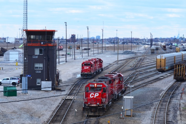 seen from a bridge, two bright red CPR train engines on tracks, beside the watch tower