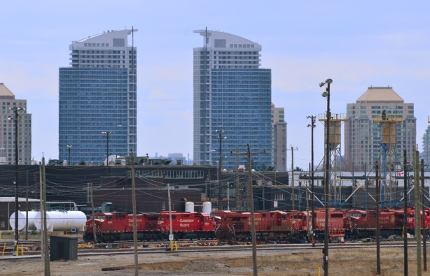 across the tracks, lots of red CPR engines, with skyline behind