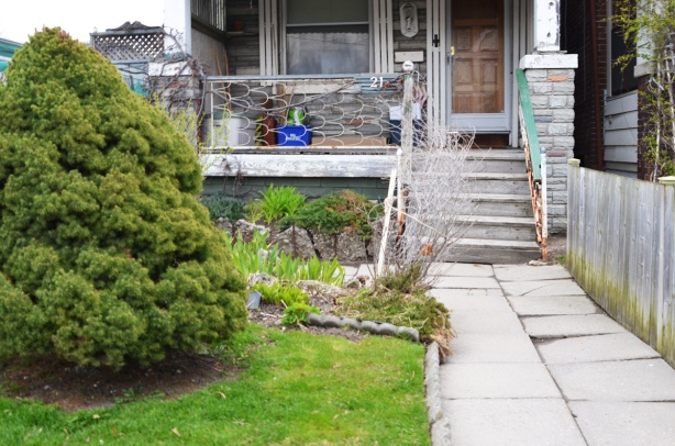 front yard and porch of a house, walkway is concrete slabs that are uneven, pine bush on grass, metal railing on porch, small garden in front of porch